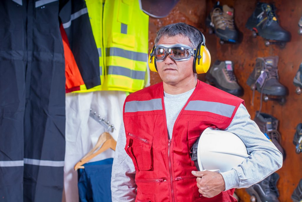 Worker with helm under arm, googles, and hearing protection looking straight