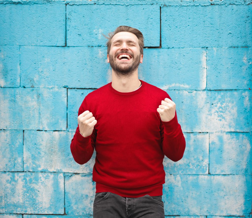 HAppy man in the red shirt in front of the blue wall celebrating