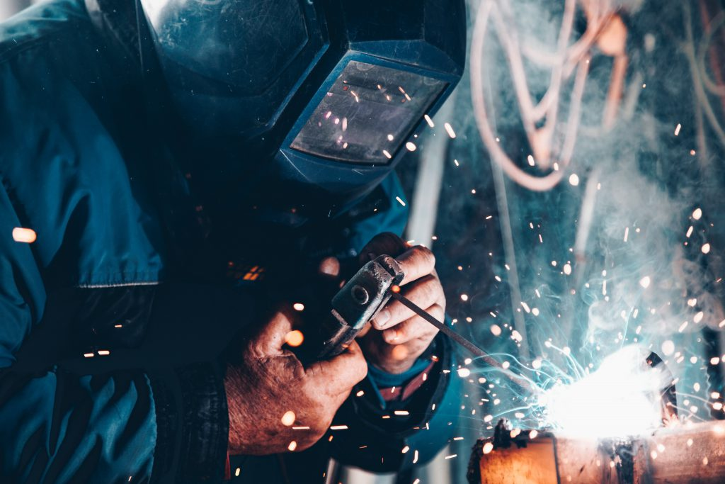 MAn welding with a mask in the factory