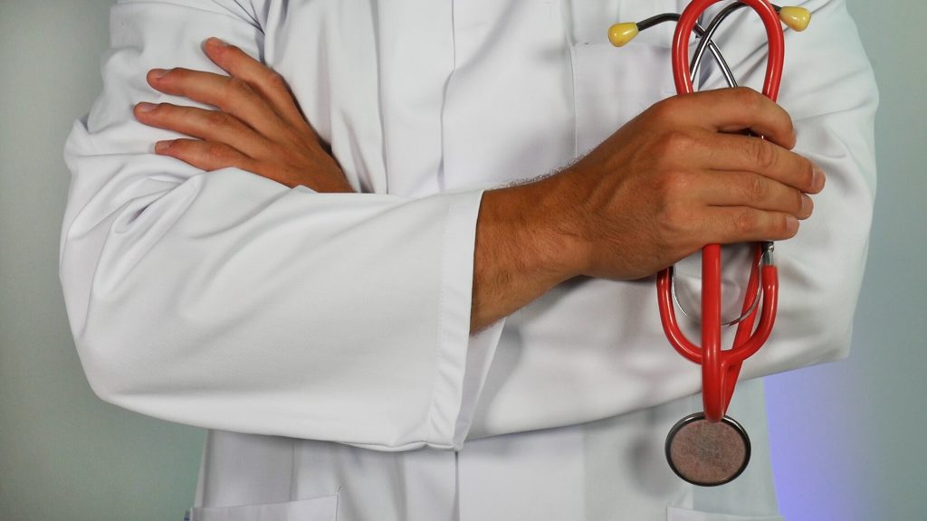 Doctor in white matle with his hands crossed looking at the camera